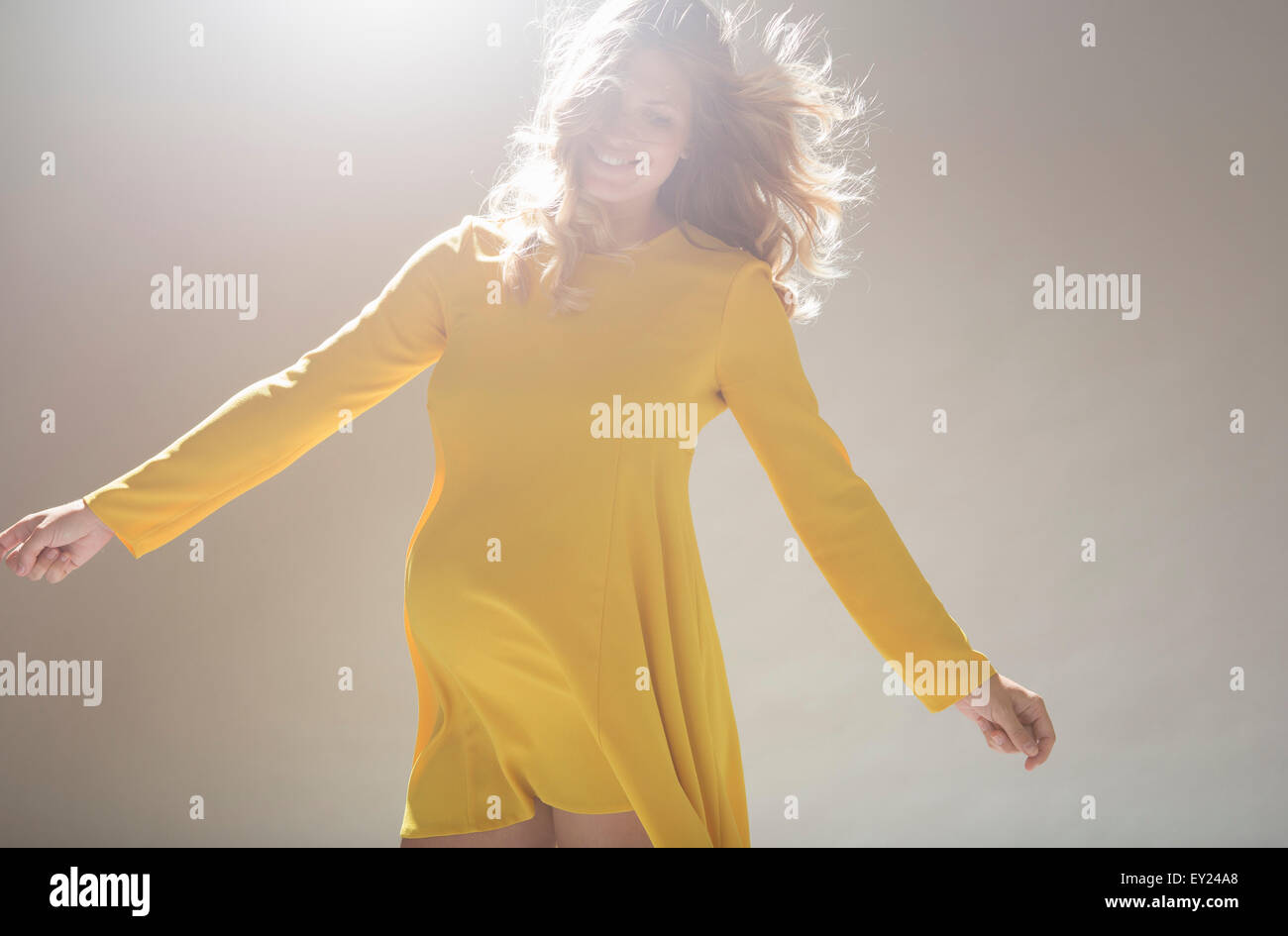 Studio portrait of pregnant young woman twirling around - Stock Image