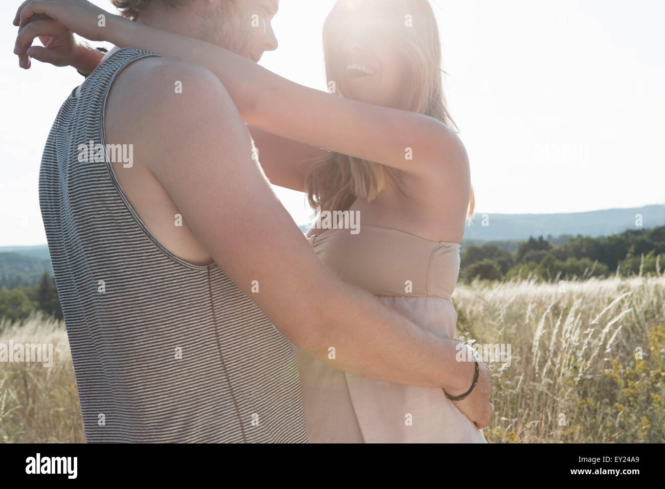 Pregnant young woman and boyfriend hugging in field - Stock Image