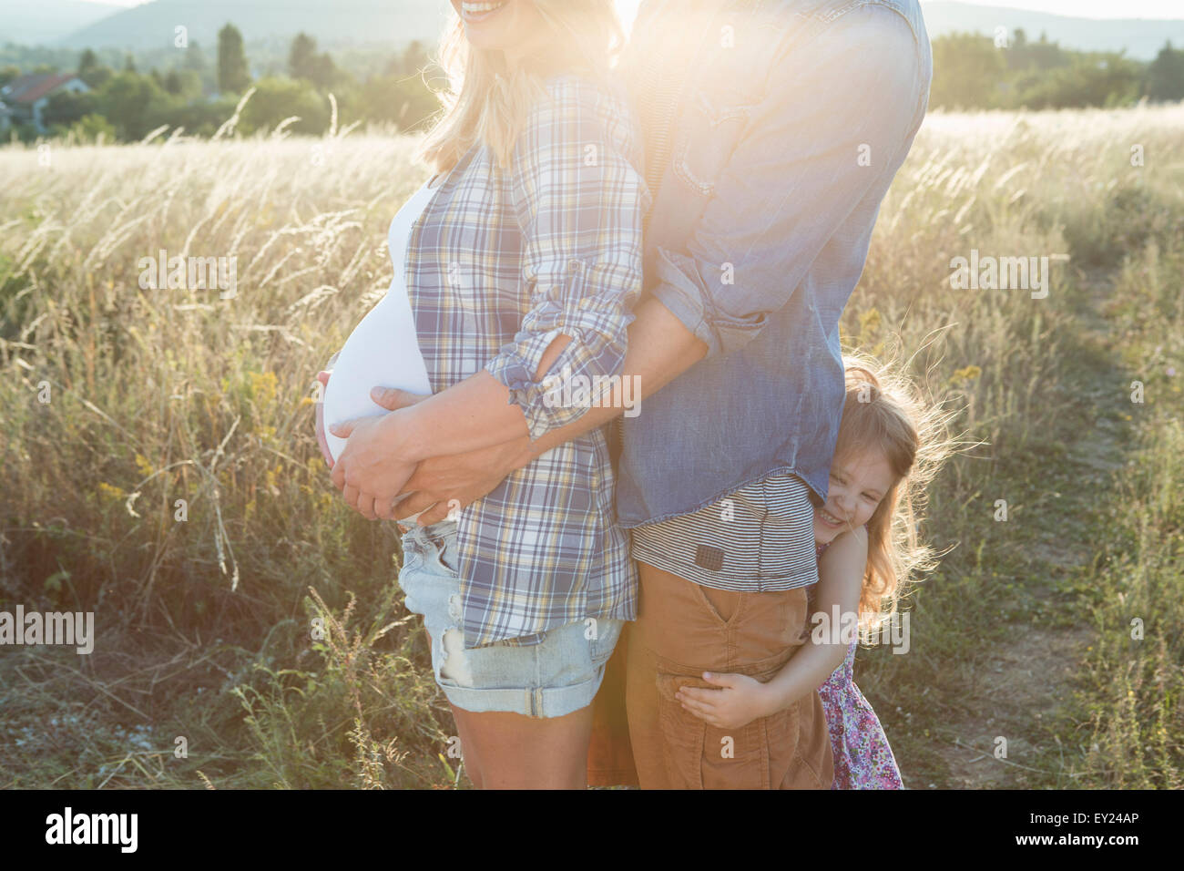 Pregnant young couple and daughter with arms around each other in field - Stock Image