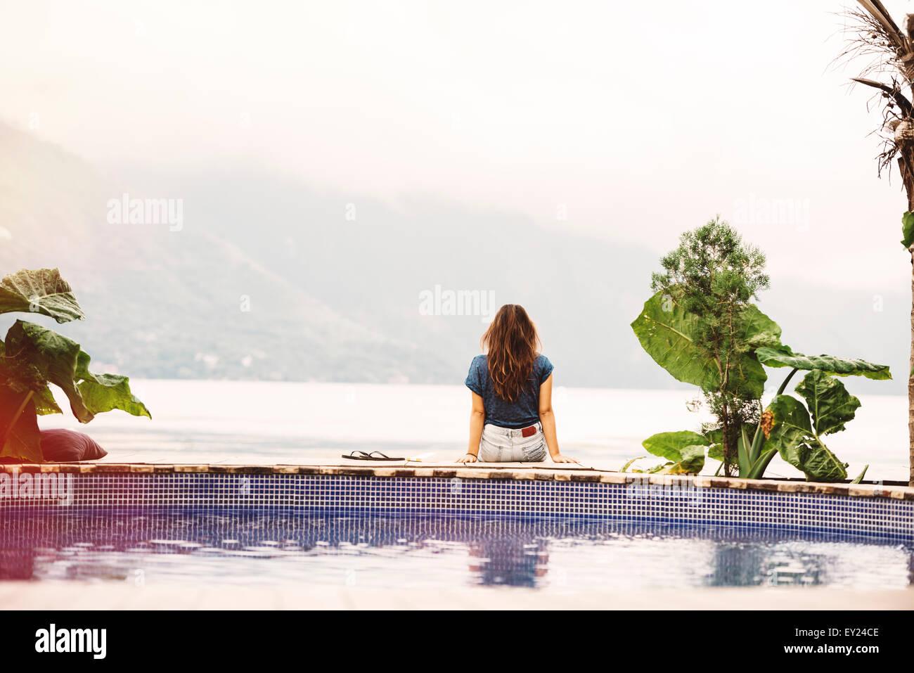 Young woman sitting on edge of pool, San Pedro, Lake Atitlan, Guatemala - Stock Image