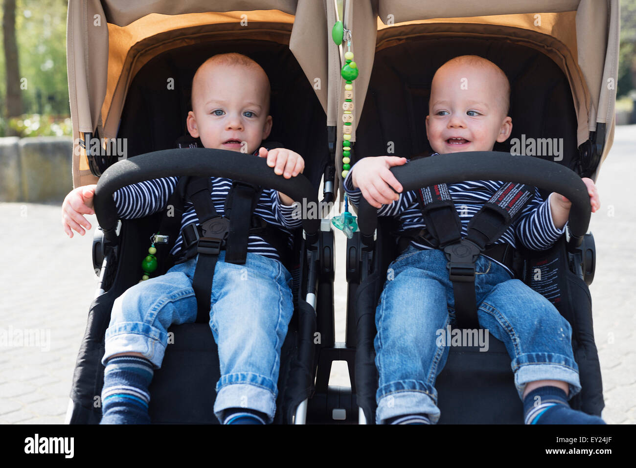 Portrait of baby twin brothers in pushchairs at park - Stock Image