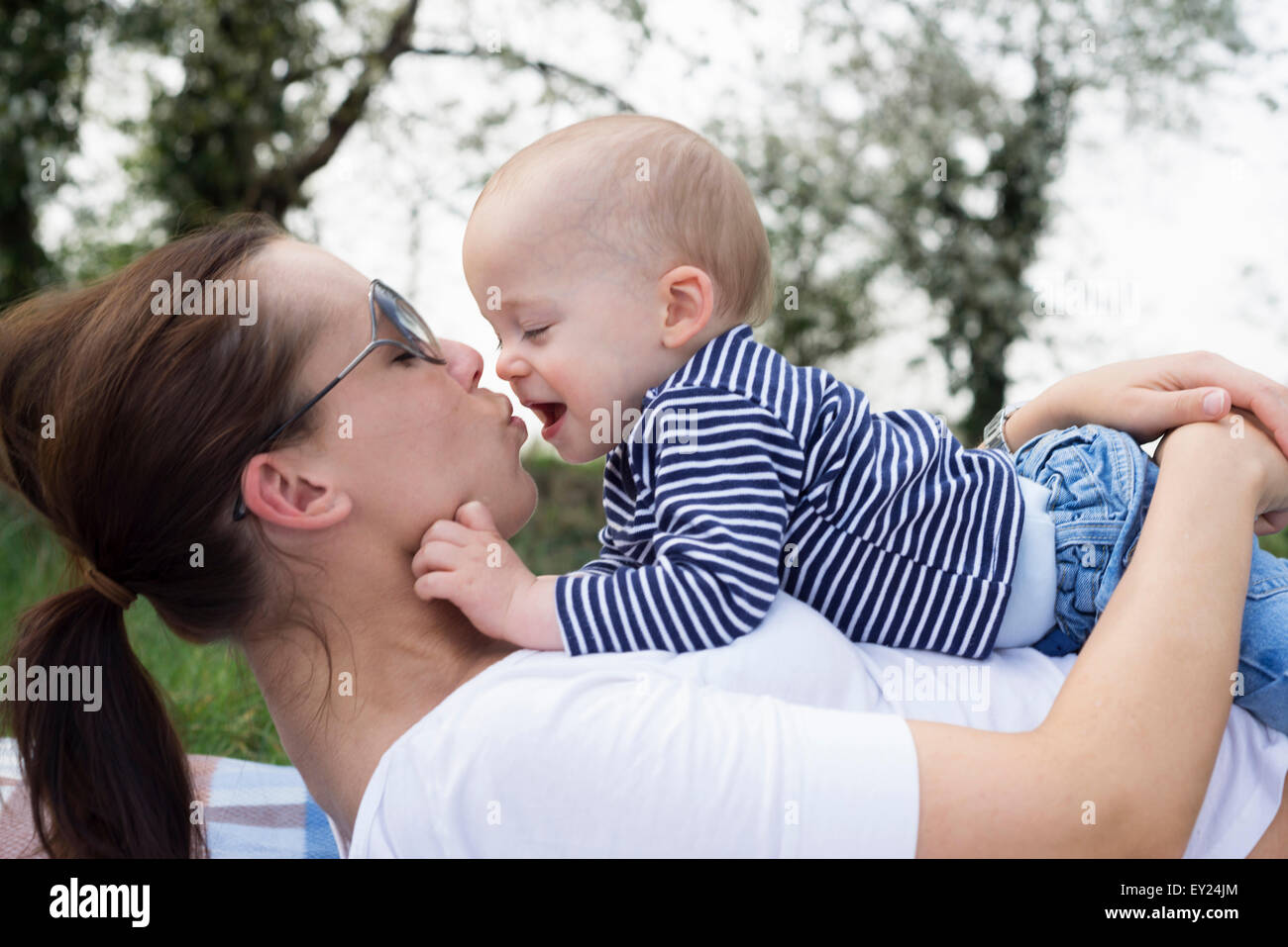 Baby boy lying on top of mother in field - Stock Image