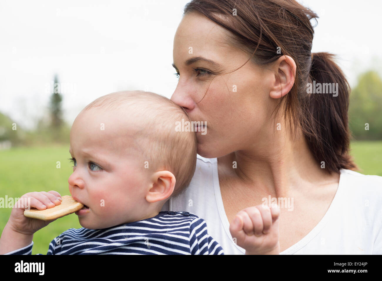 Portrait of young mother kissing baby son in field - Stock Image