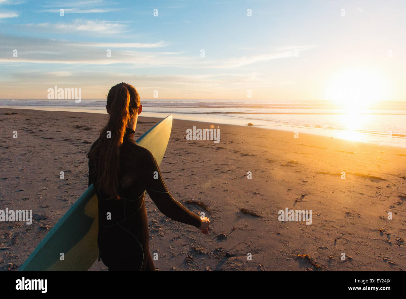 Rear view of female surfer walking on beach toward sea, Cardiff-By-The-Sea, California, USA - Stock Image