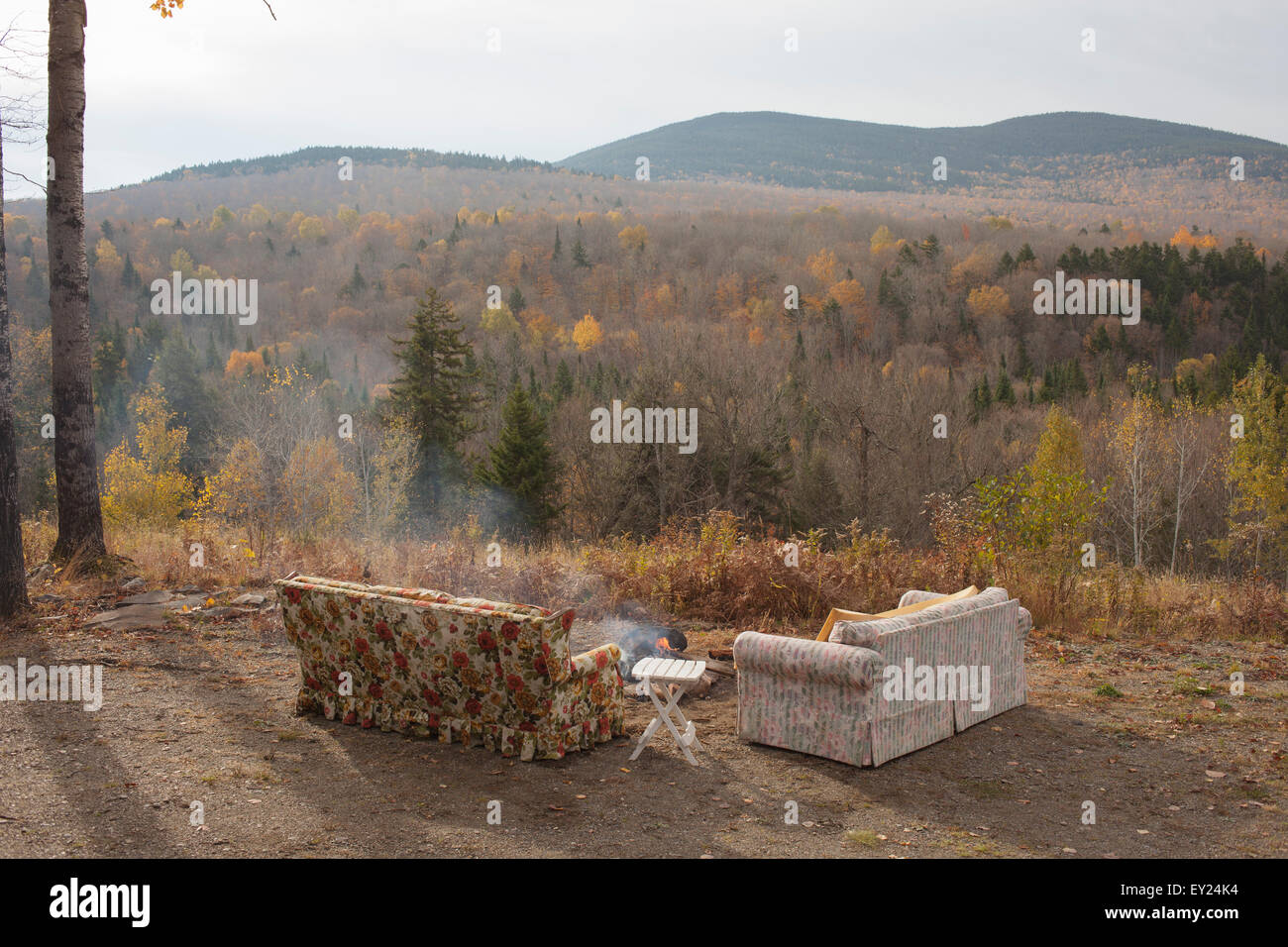 Two sofas and campfire with autumn forest view, Maine, USA - Stock Image
