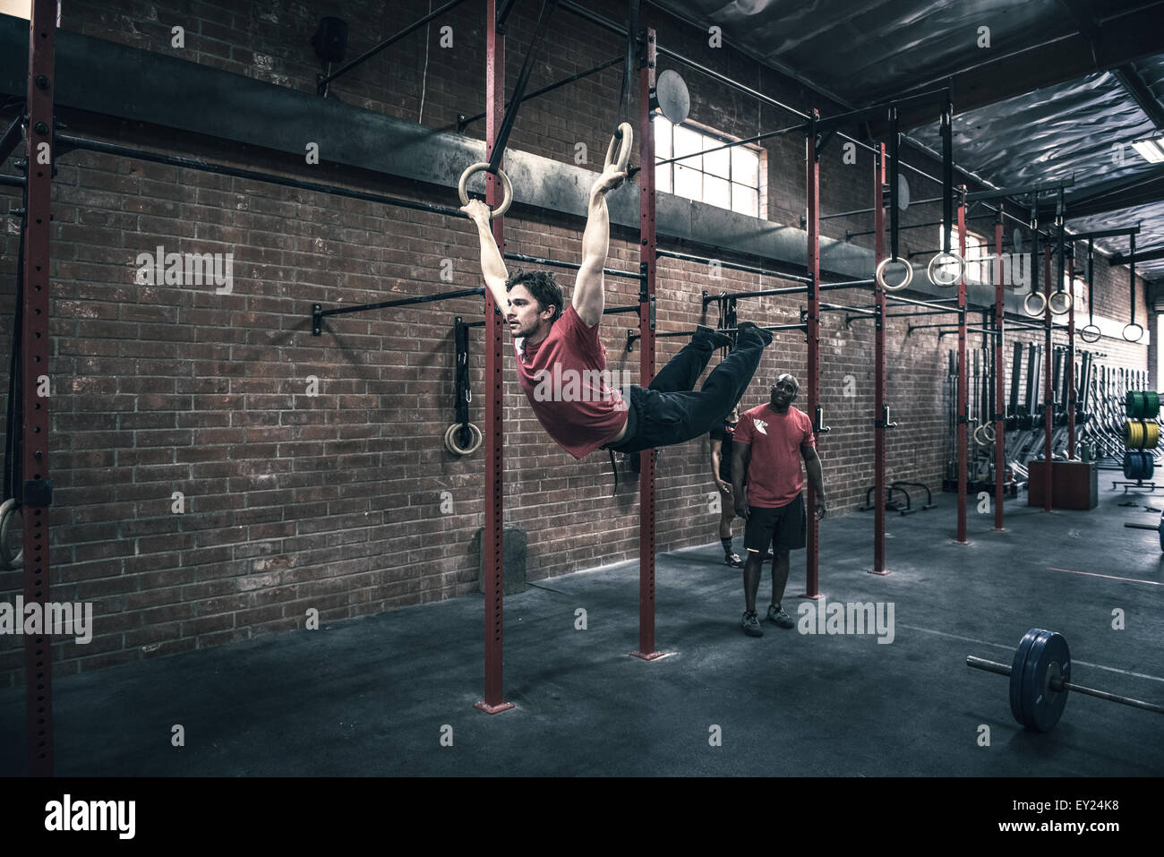 Young man swinging on gym rings in gym Stock Photo