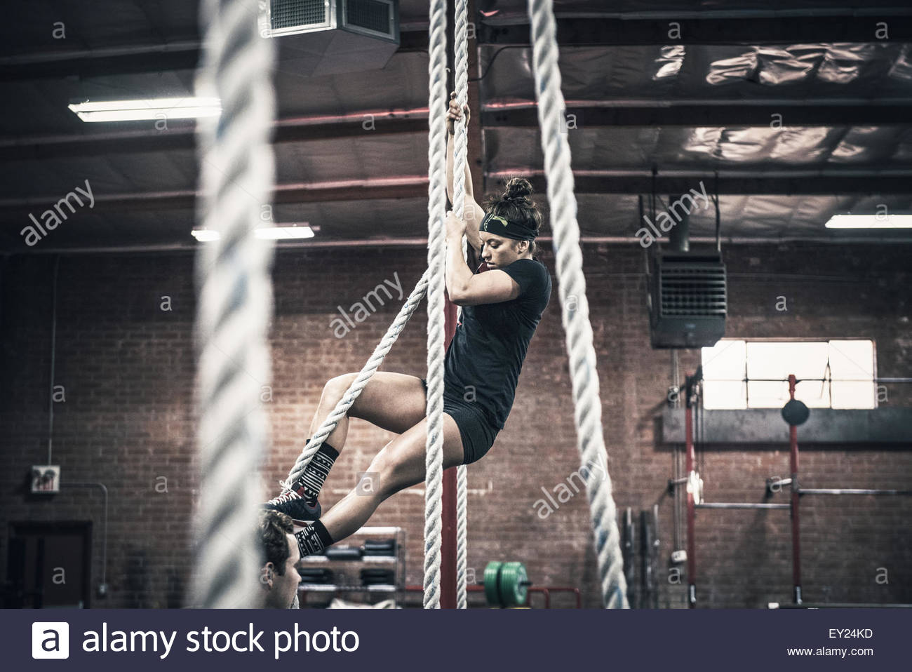Young woman climbing rope in gymStock Photo