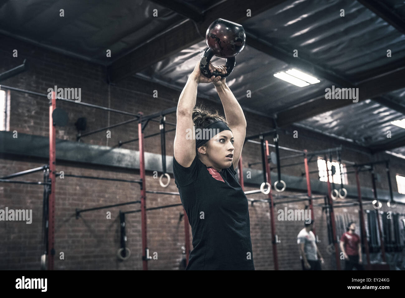 Young woman holding up kettle bells in gym - Stock Image