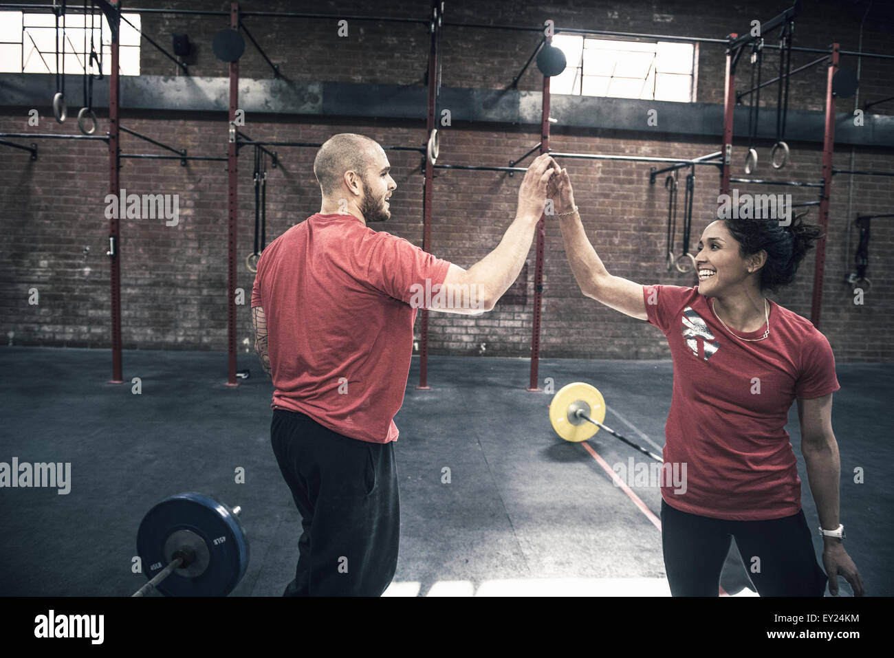 Young man and woman giving each other high five in gym - Stock Image