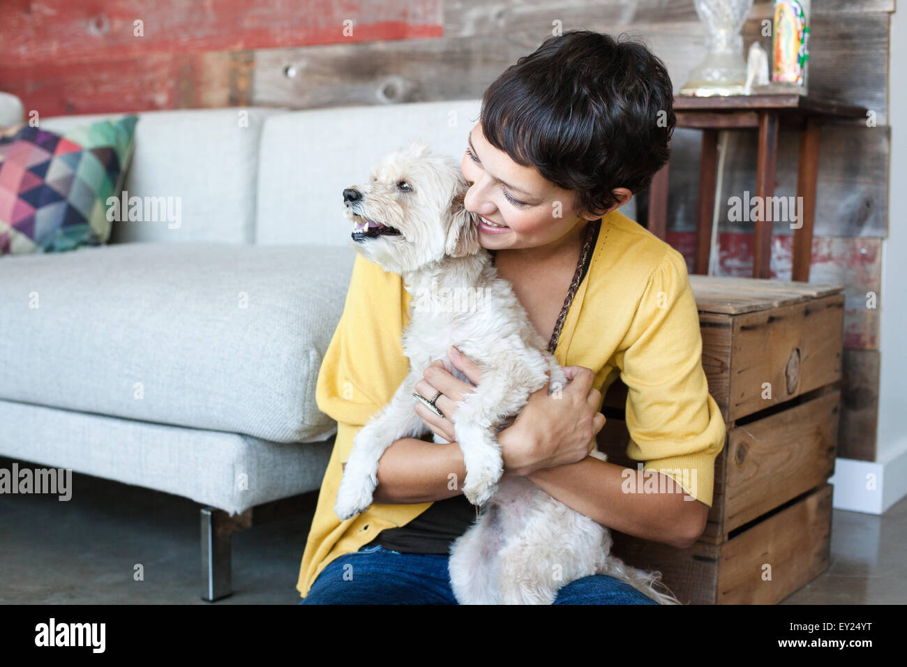 Young woman hugging dog on living room floor - Stock Image