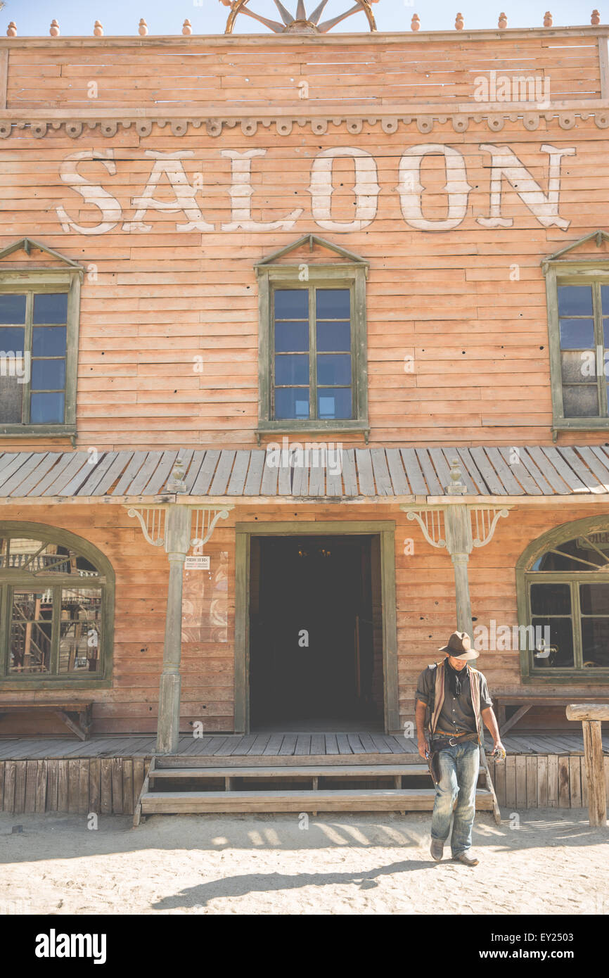 Cowboy in front of saloon building on wild west film set, Fort Bravo, Tabernas, Almeria, Spain - Stock Image