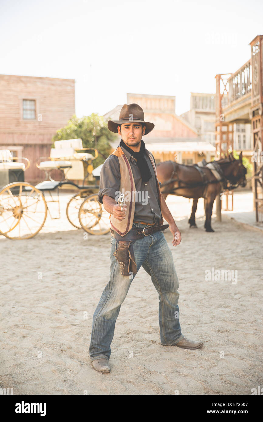 Portrait of cowboy pointing gun on wild west film set, Fort Bravo, Tabernas, Almeria, Spain - Stock Image