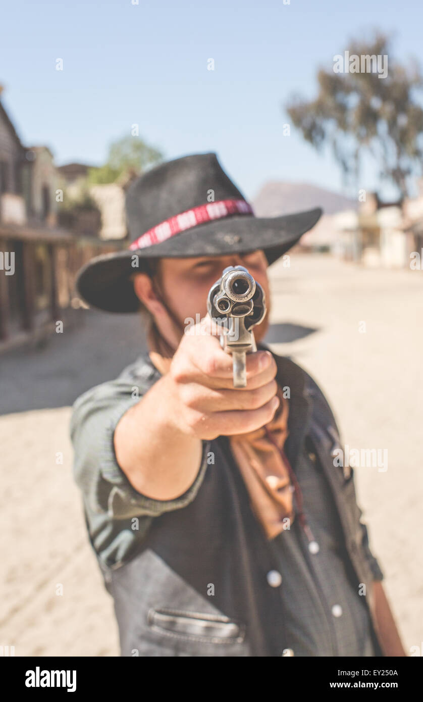 Cowboy pointing handgun on wild west film set, Fort Bravo, Tabernas, Almeria, Spain - Stock Image