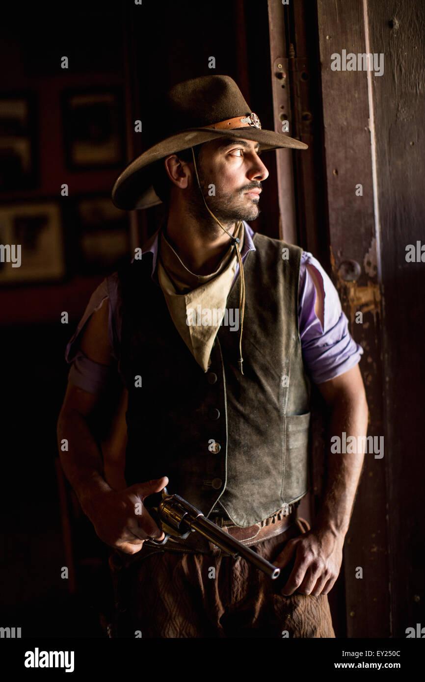 Portrait of cowboy holding handgun in doorway on wild west film set, Fort Bravo, Tabernas, Almeria, Spain - Stock Image