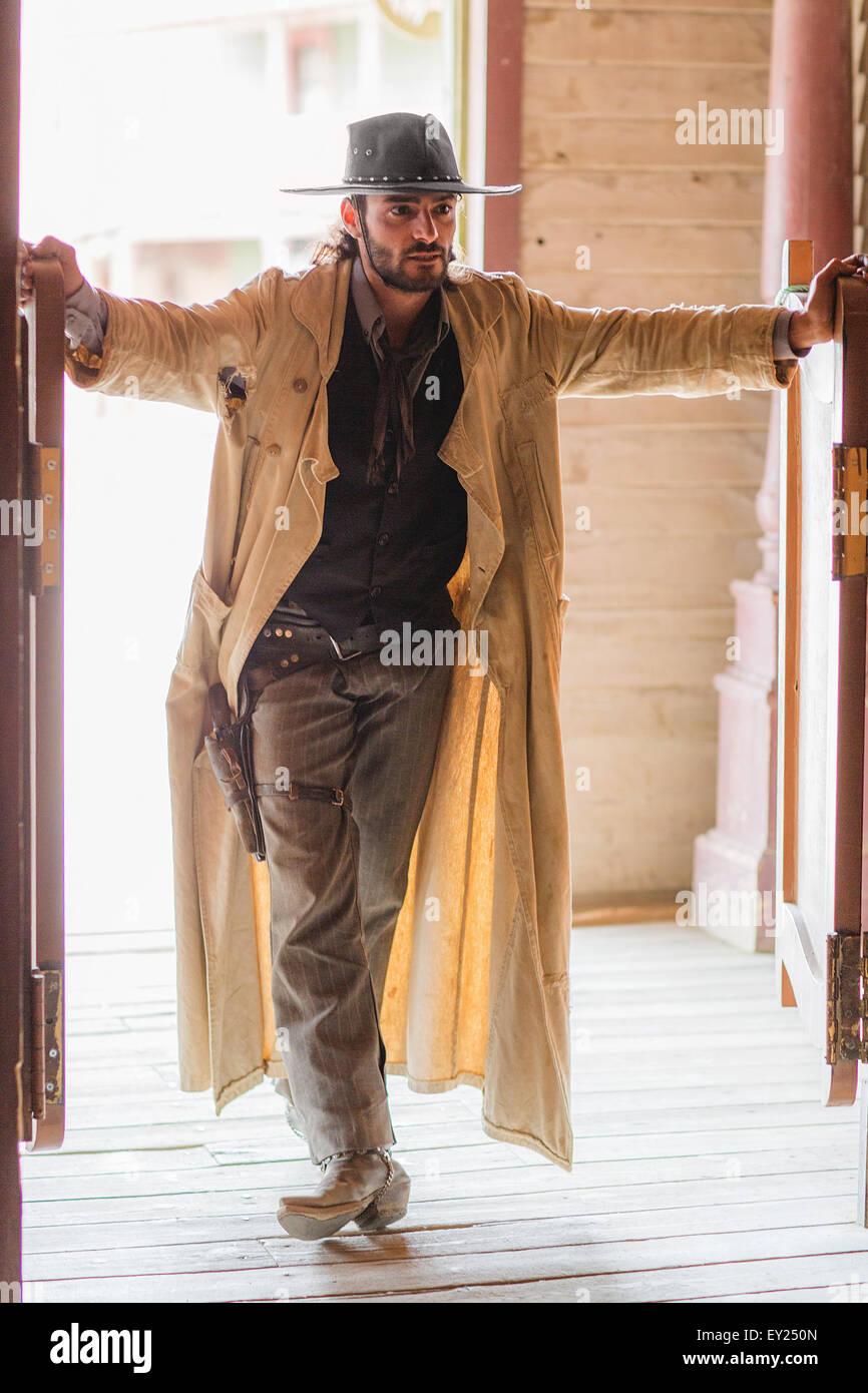 Cowboy standing in saloon doorway on wild west film set, Fort Bravo, Tabernas, Almeria, Spain - Stock Image