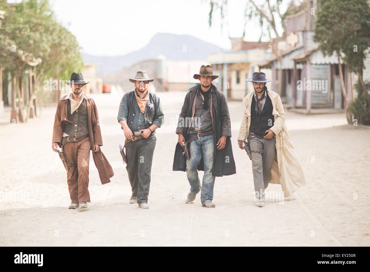 Portrait of four cowboys walking along street on wild west film set, Fort Bravo, Tabernas, Almeria, Spain - Stock Image