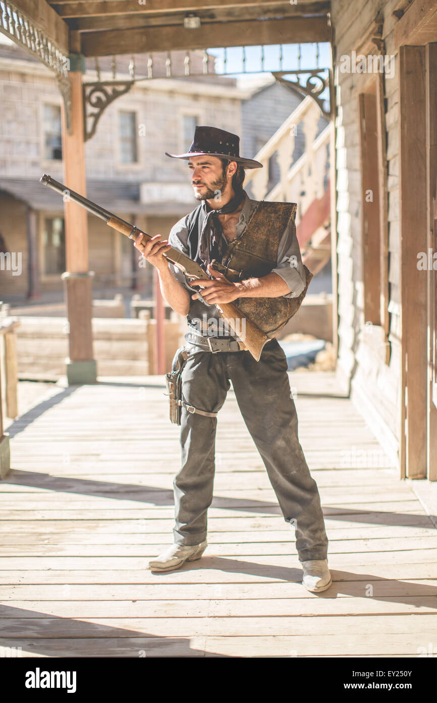 Portrait of cowboy holding up shotgun on wild west film set, Fort Bravo, Tabernas, Almeria, Spain - Stock Image