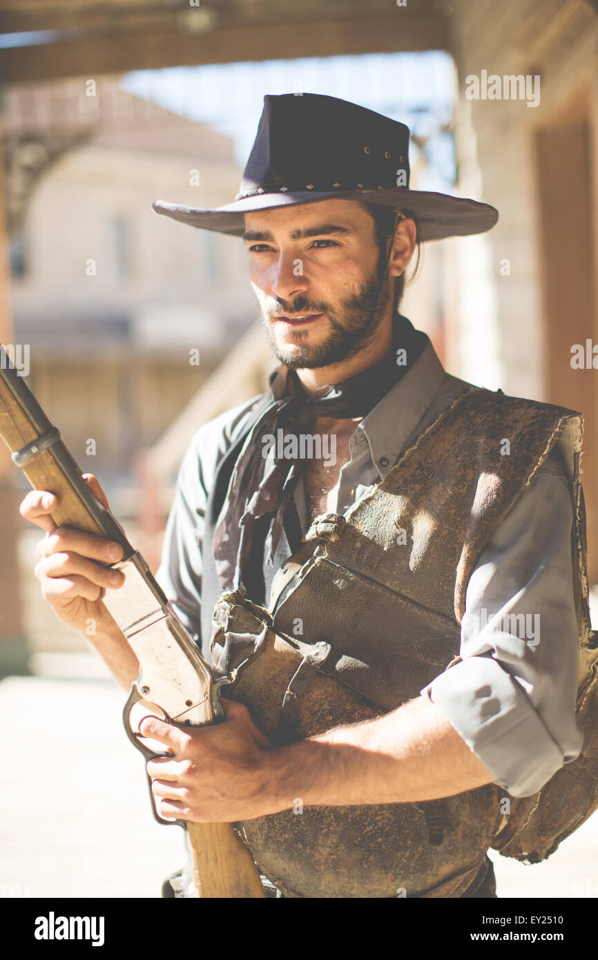 Cowboy holding up shotgun on wild west film set, Fort Bravo, Tabernas, Almeria, Spain - Stock Image