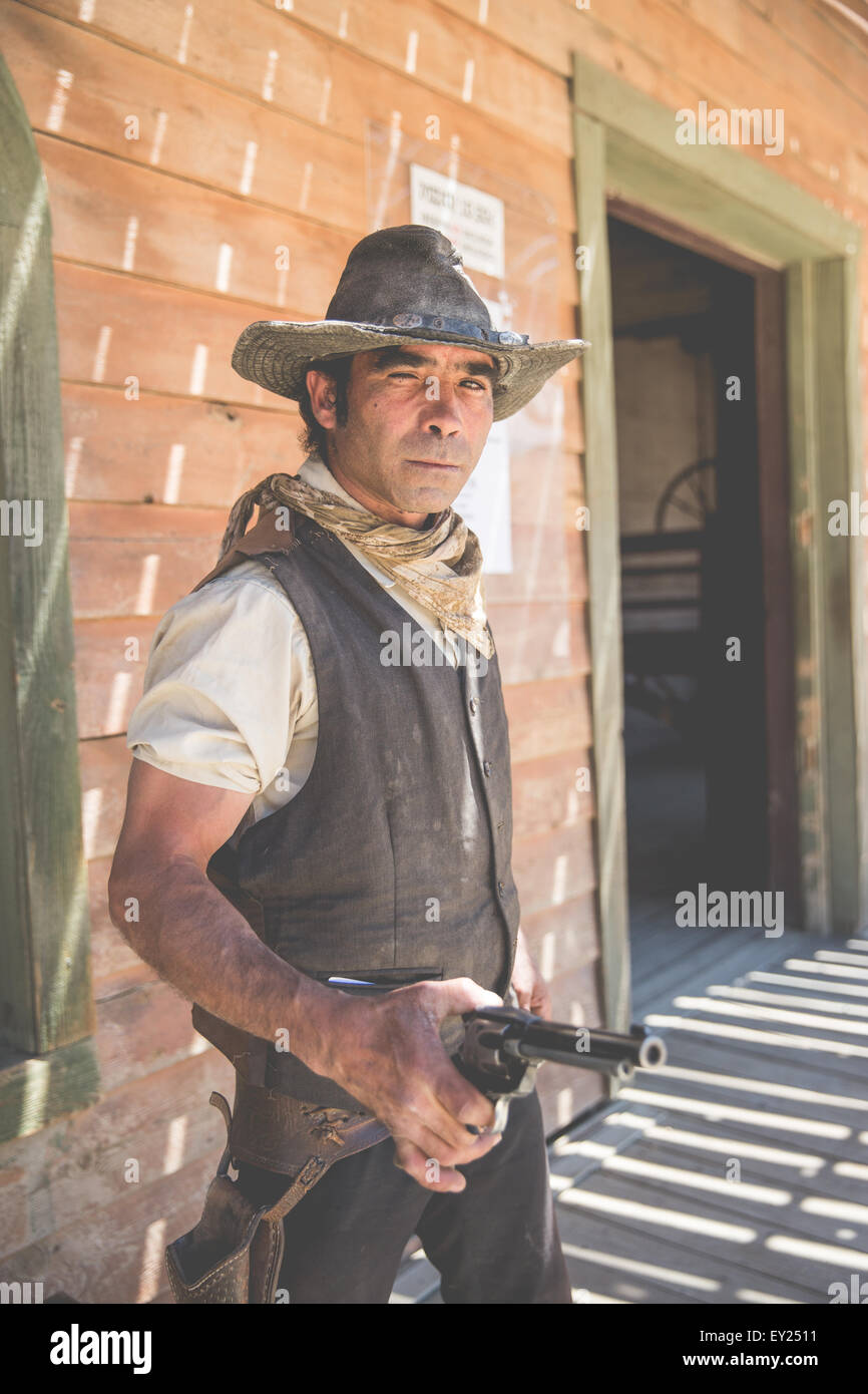 Portrait of cowboy holding up handgun on wild west film set, Fort Bravo, Tabernas, Almeria, Spain - Stock Image