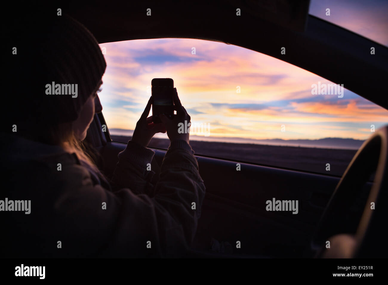 Young woman taking photograph of sunset with smartphone from inside car - Stock Image