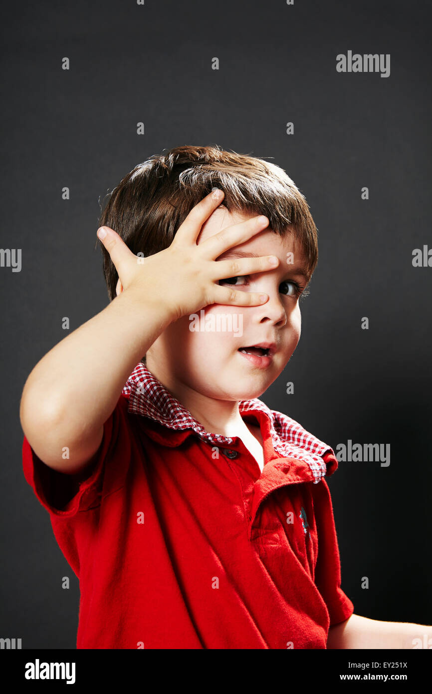 Portrait of young boy with hand on face - Stock Image
