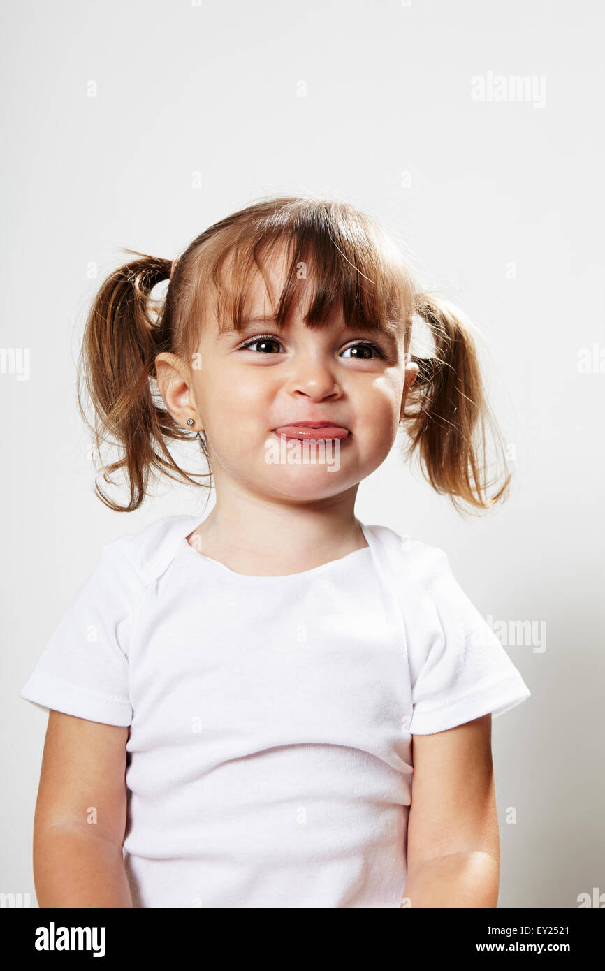 Portrait of young girl with pigtails, making faces - Stock Image
