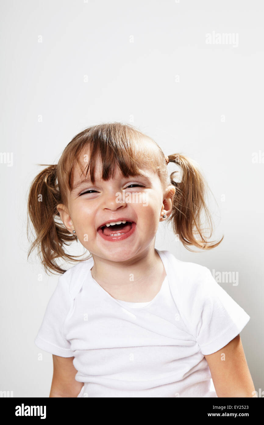 Portrait of young girl with pigtails, laughing - Stock Image