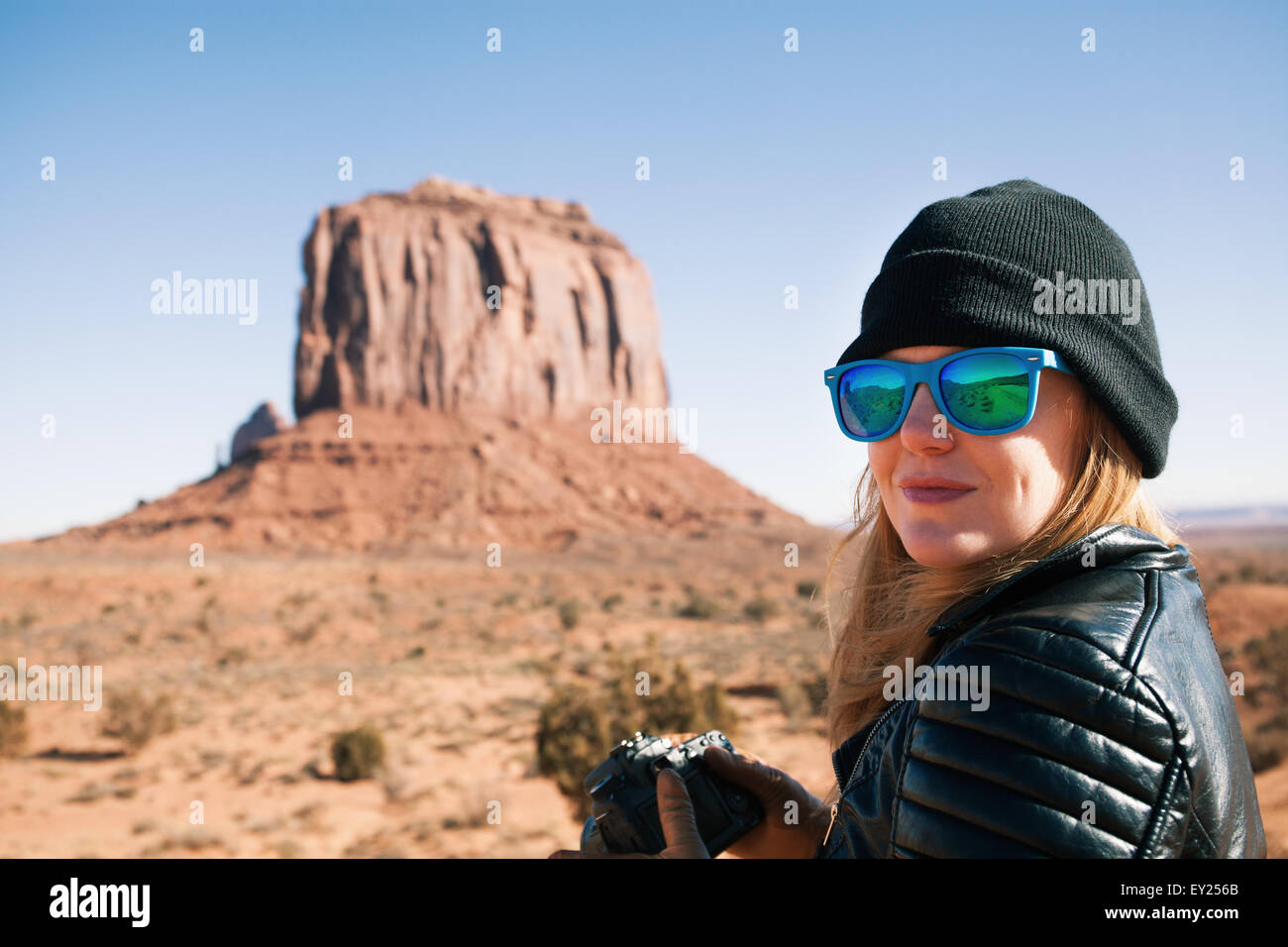 Portrait of woman in blue sunglasses, Monument Valley, Utah, USA - Stock Image