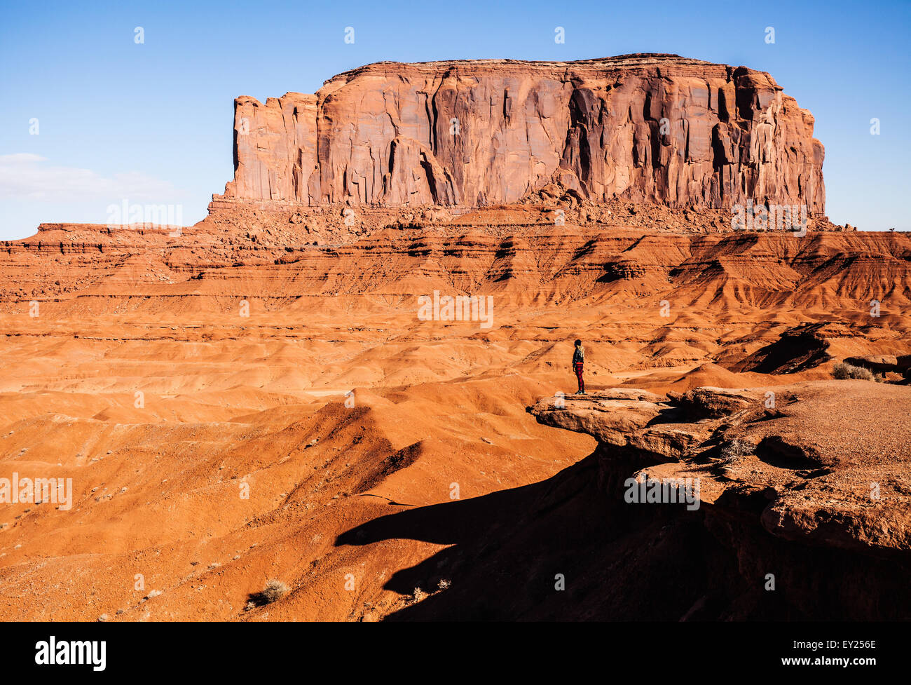 Distant view of woman looking out over  Monument Valley, Utah, USA - Stock Image