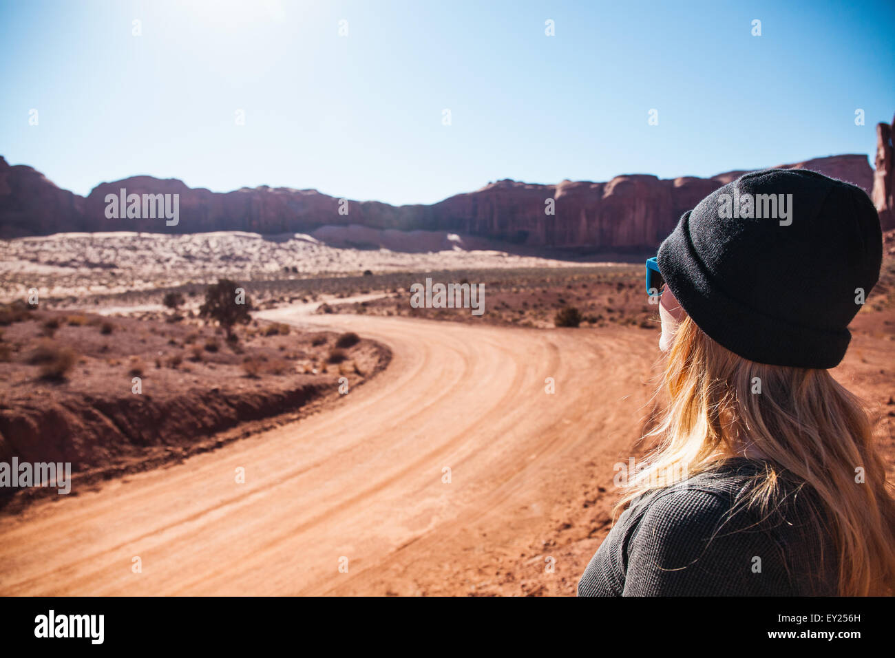 Mid adult woman looking out at rural dirt road, Monument Valley, Utah, USA - Stock Image