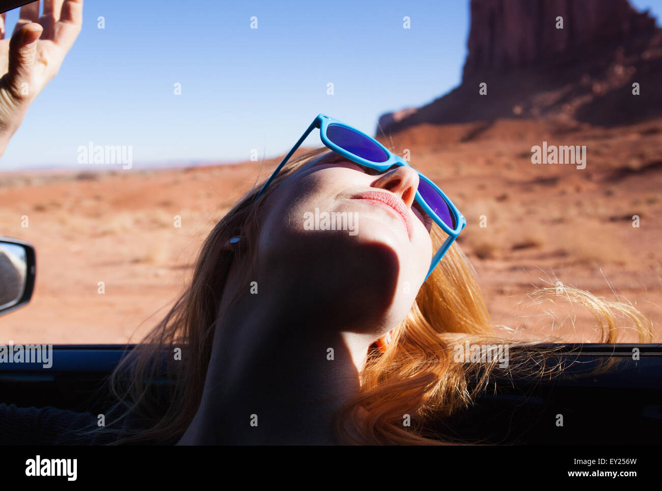 Woman leaning back out of car window, Monument Valley, Utah, USA - Stock Image