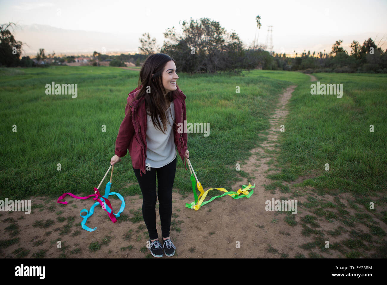 Young woman standing in field holding dance ribbons - Stock Image