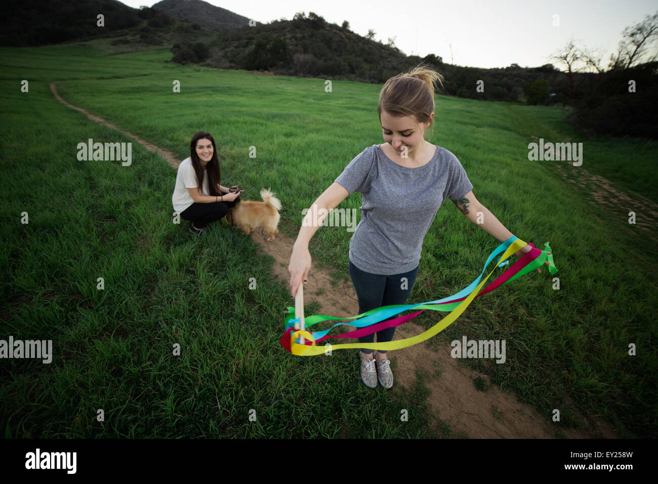 Young woman standing in field untangling dance ribbons - Stock Image