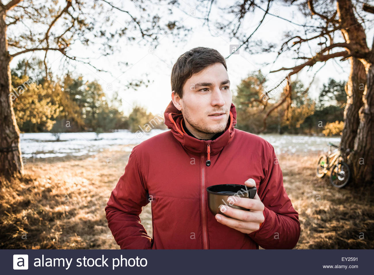 Young male hiker drinking coffee in lakeside forest - Stock Image