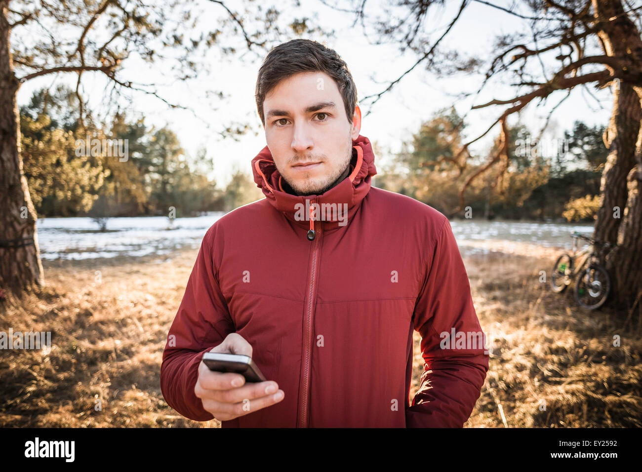 Young male hiker using smartphone in lakeside forest - Stock Image