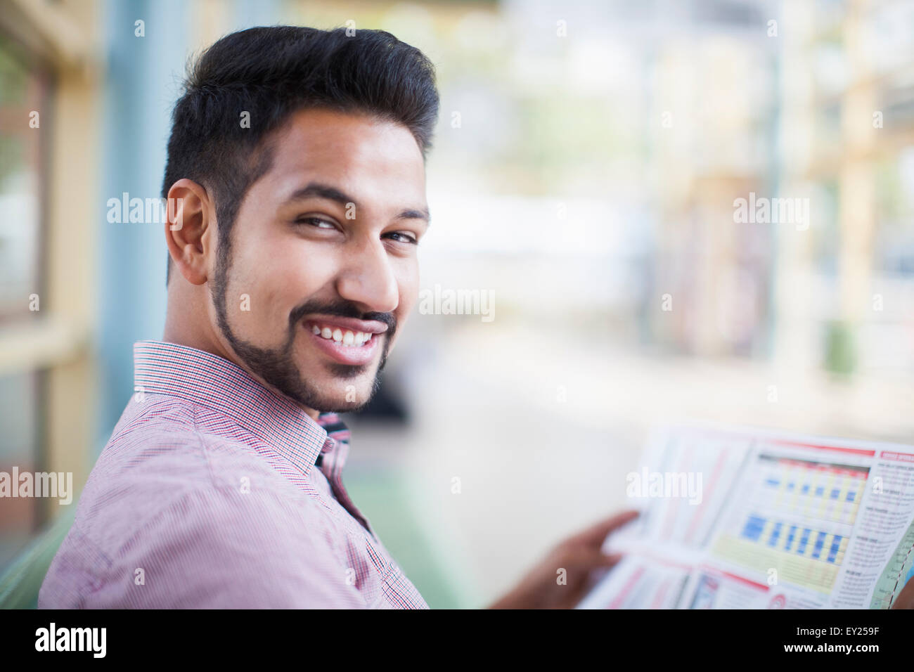Young businessman reading newspaper in train station - Stock Image