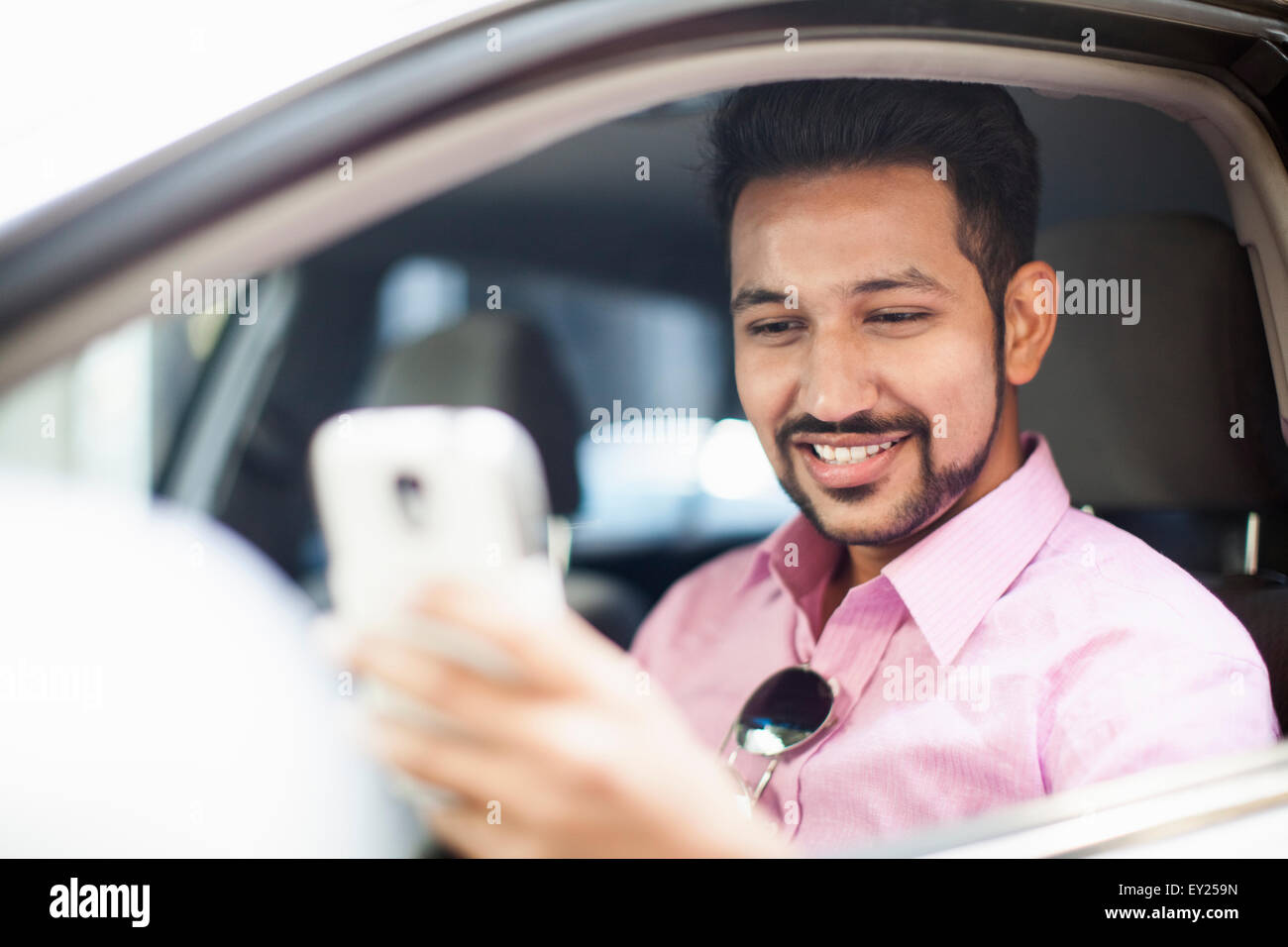Young businessman reading smartphone text at car window - Stock Image