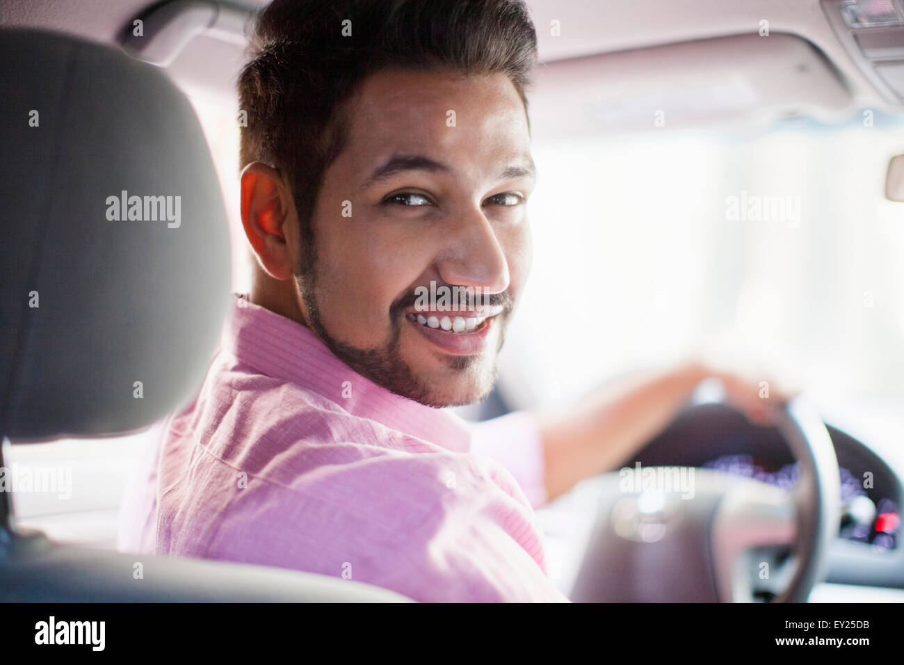 Portrait of young businessman looking over his shoulder in car - Stock Image