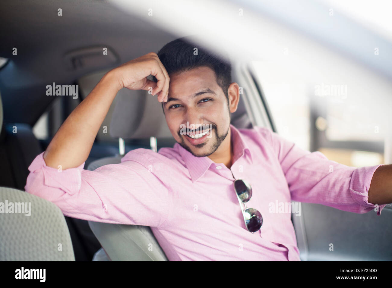 Portrait of young businessman in car - Stock Image