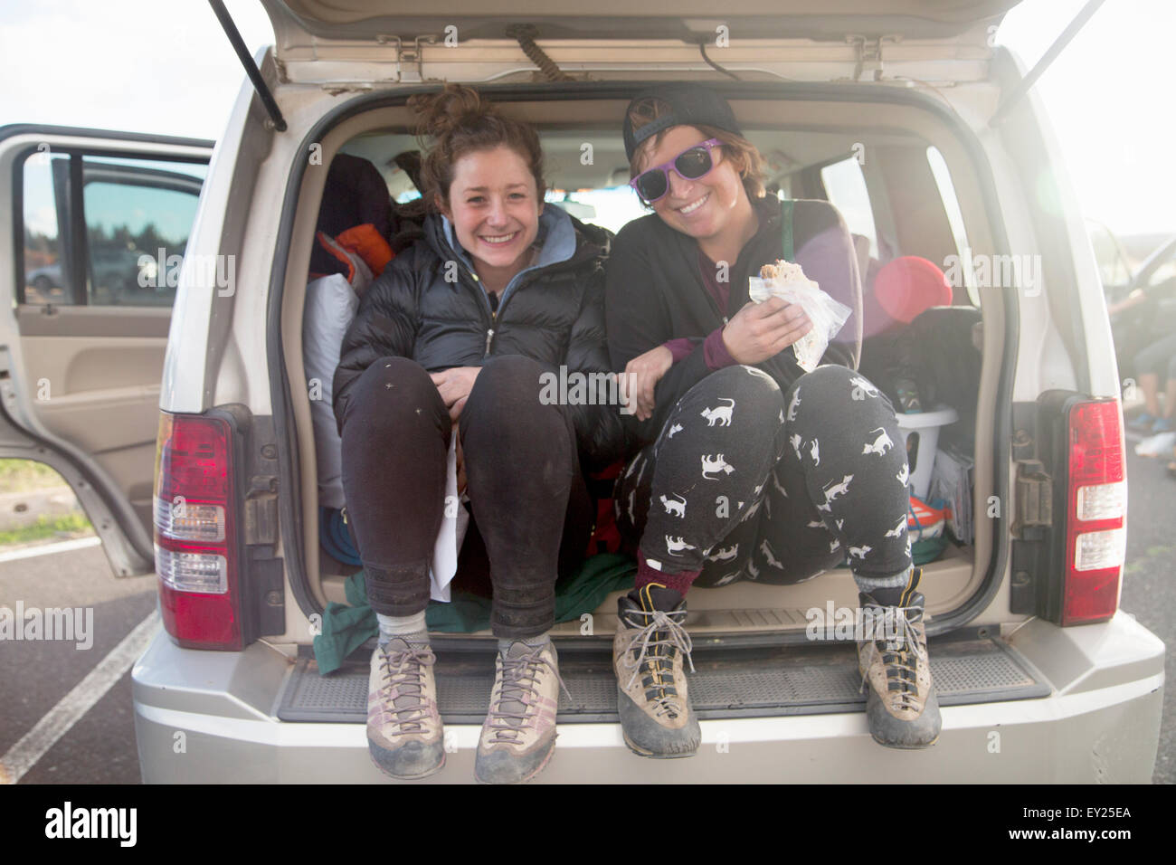 Hikers taking break at back of car, Smith Rock State Park, Oregon, US - Stock Image