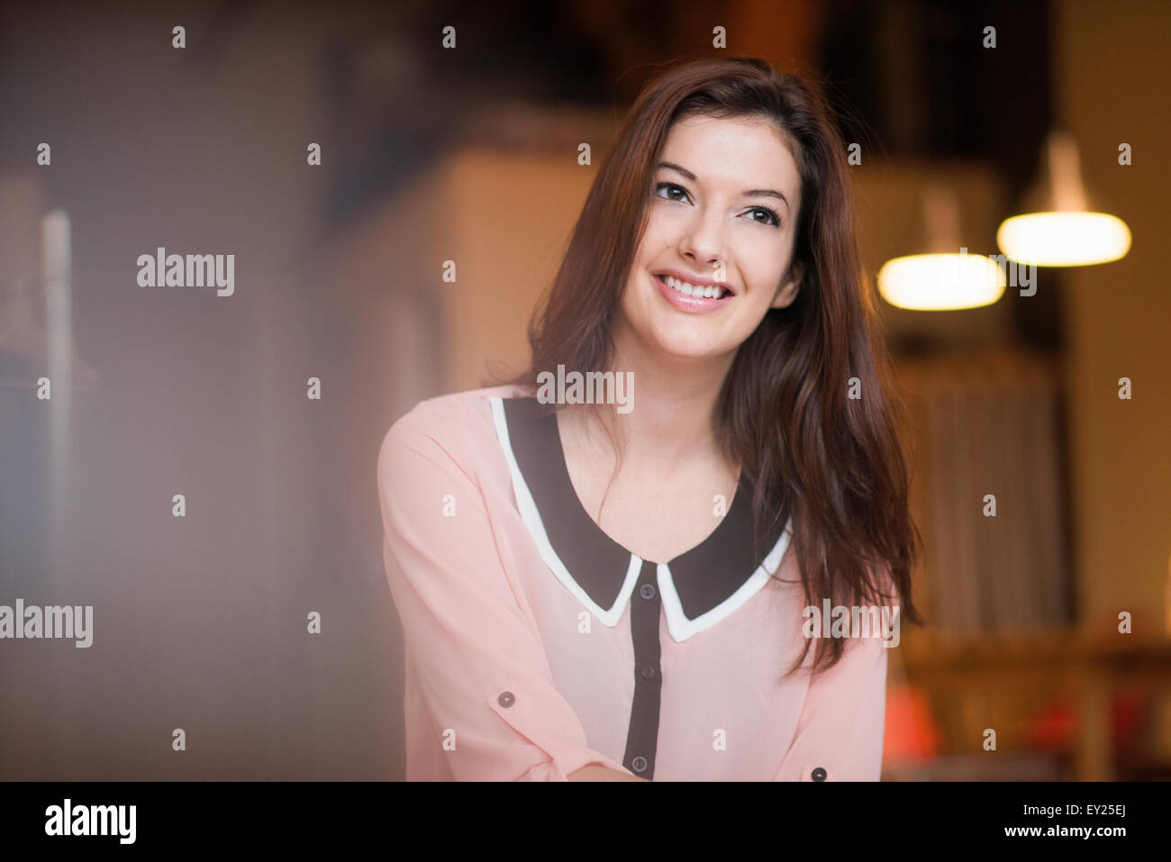 Portrait of young woman with long dark hair, smiling - Stock Image