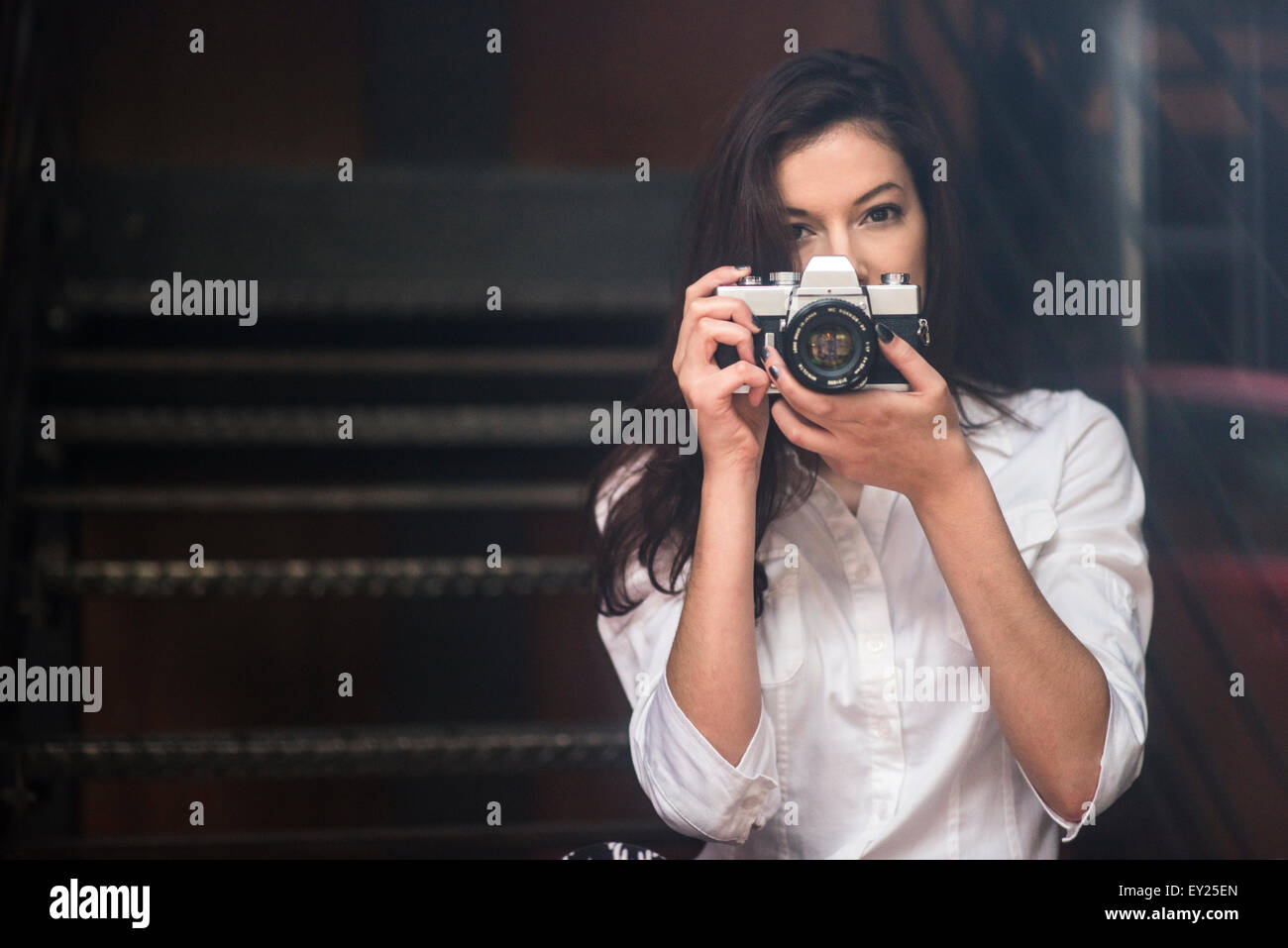 Young woman taking photograph with SLR camera - Stock Image