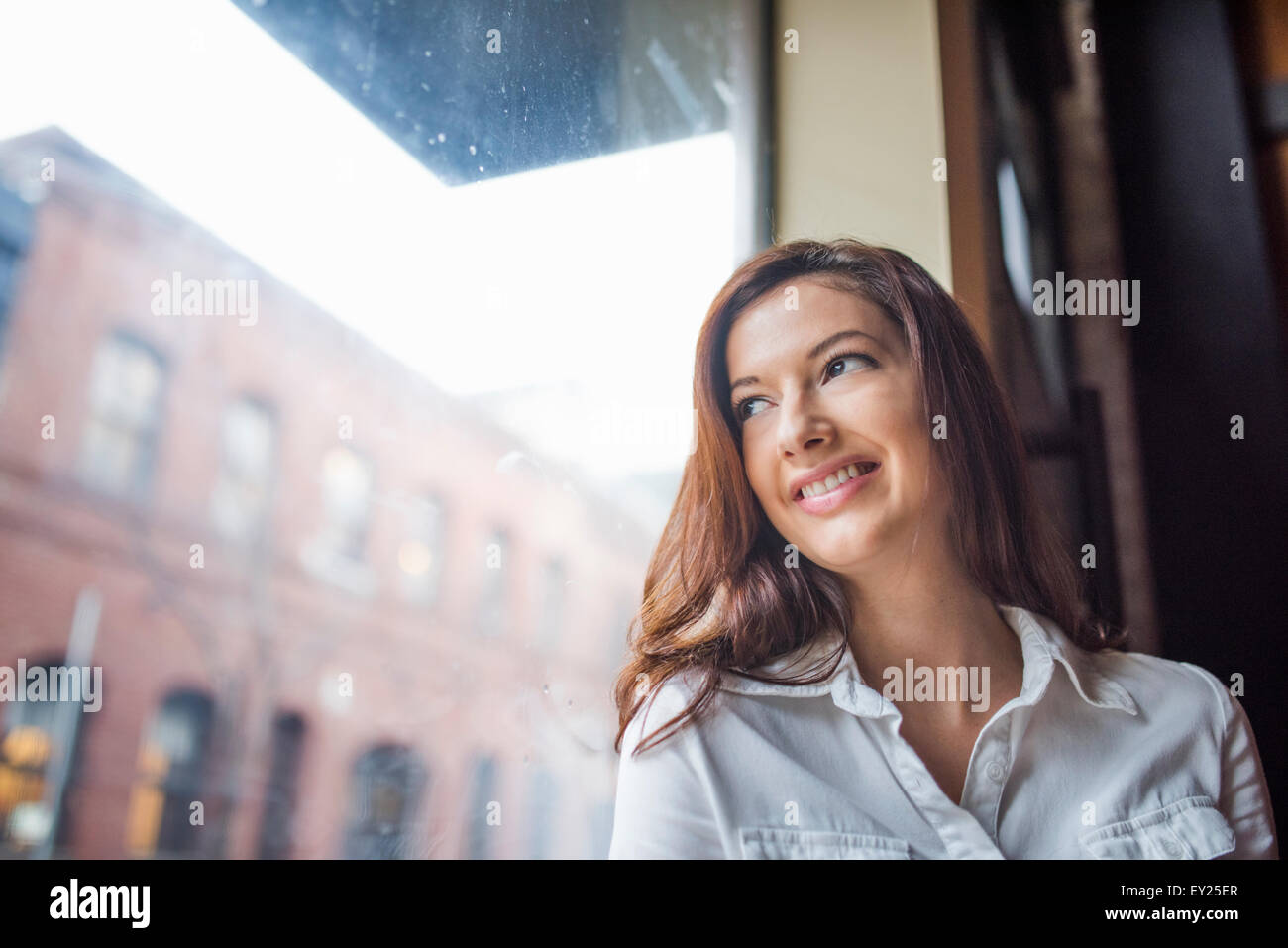 Portrait of young woman with long dark hair, smiling, low angle view - Stock Image
