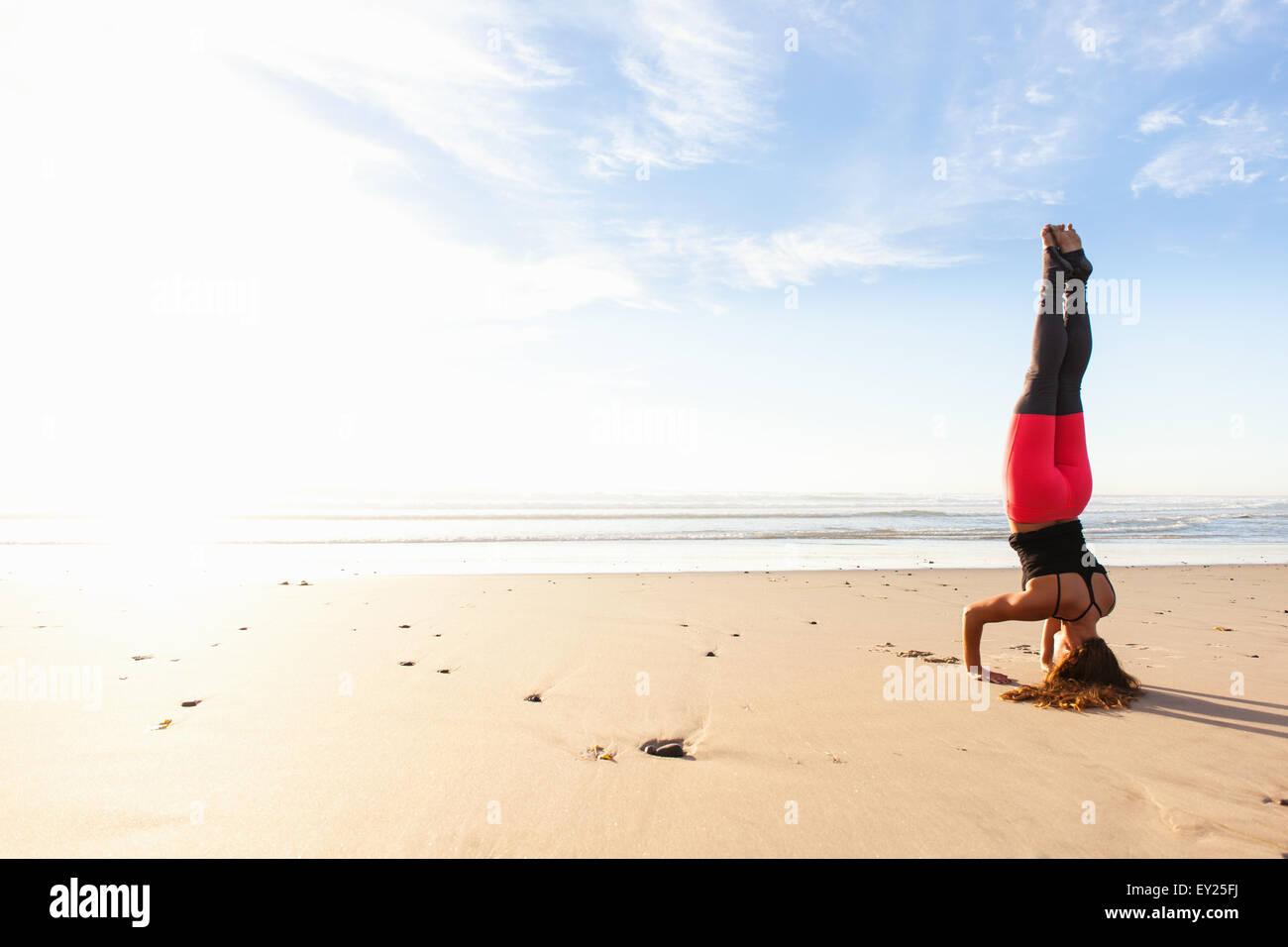 Woman in yoga pose on beach - Stock Image