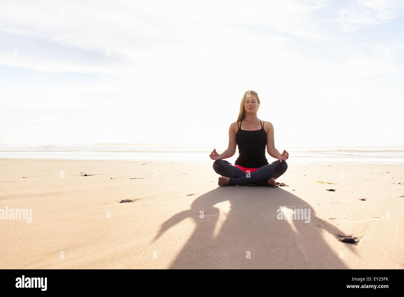 Woman in yoga pose on beach - Stock Image