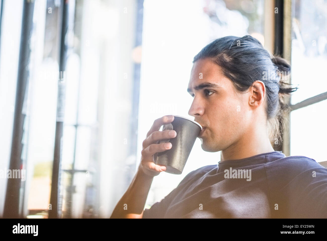 Young man drinking coffee, indoors - Stock Image