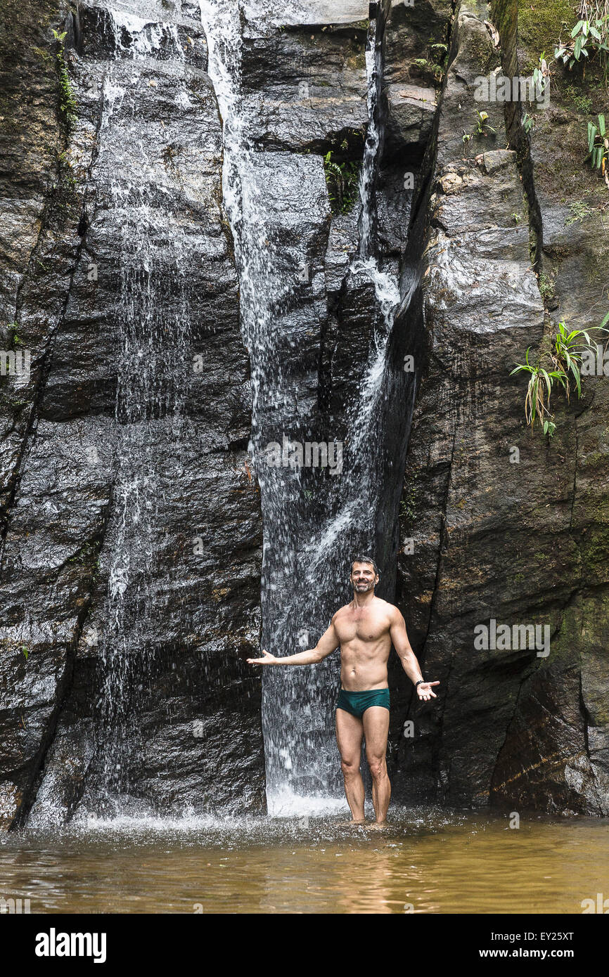 Portrait of mature man with open arms in front of waterfall, Tijuca Forest, Rio de Janeiro, Brazil - Stock Image
