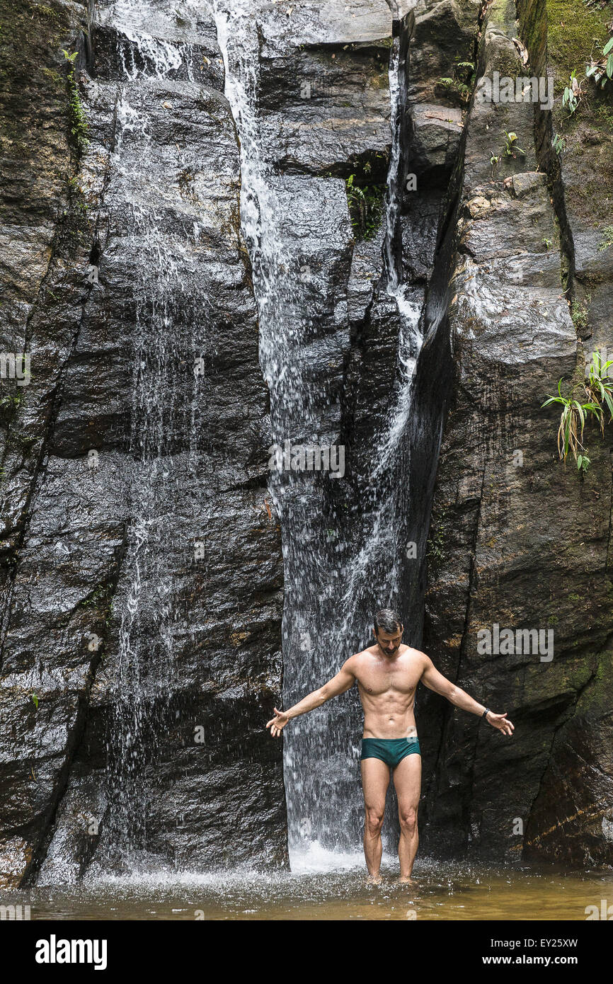 Mature man standing with open arms in front of waterfall, Tijuca Forest, Rio de Janeiro, Brazil - Stock Image