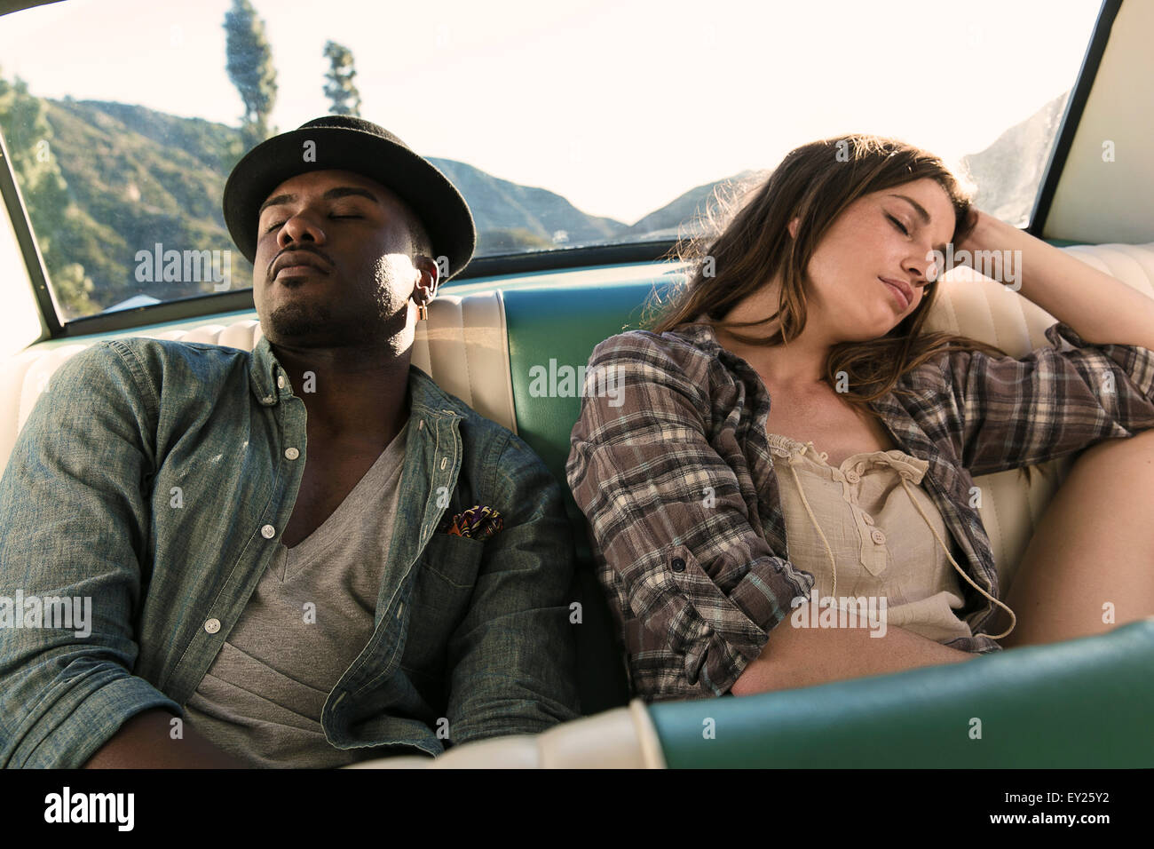 Couple asleep in back seat of car - Stock Image