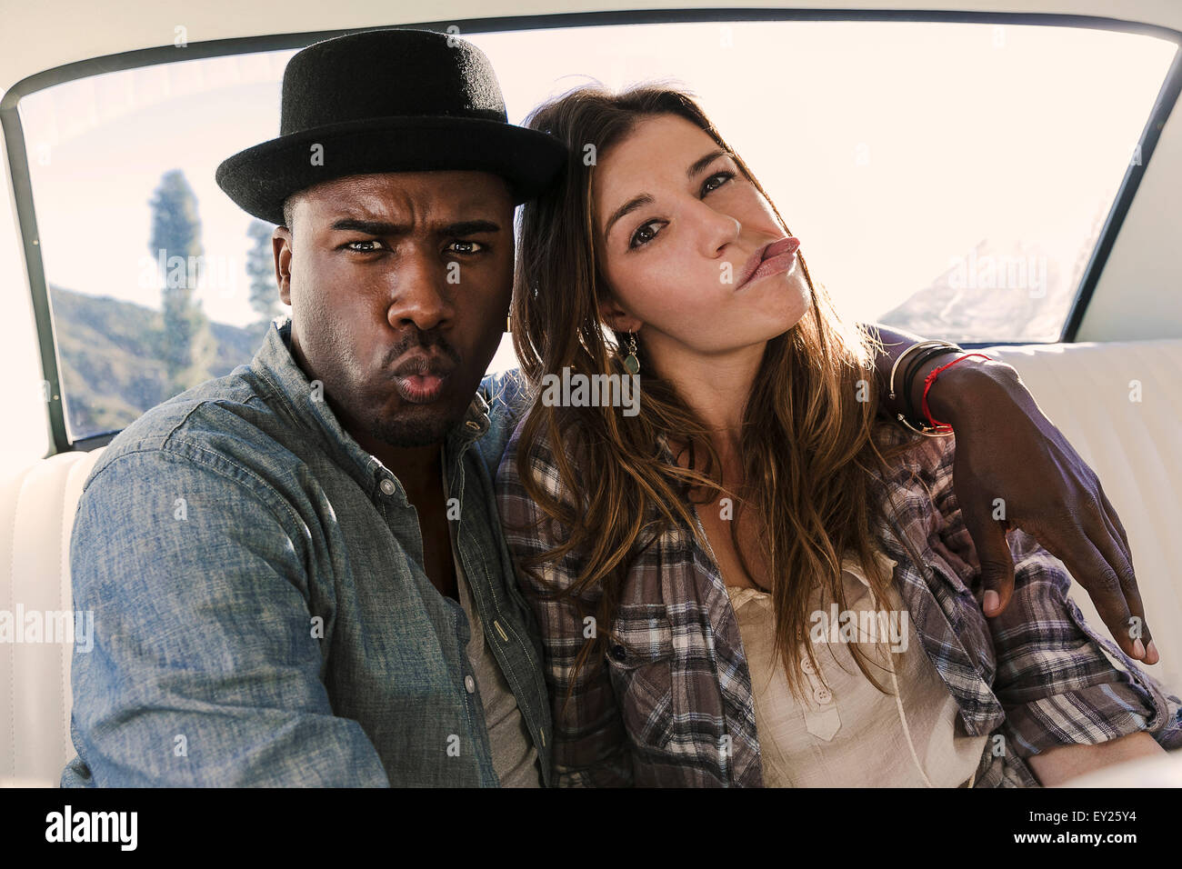 Portrait of couple pulling faces in back seat of car - Stock Image